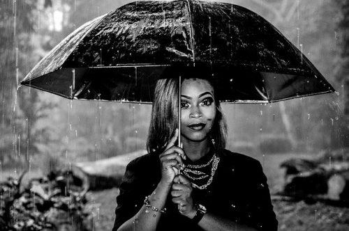 Woman unter einem Regenschirm mit Afrohaaren